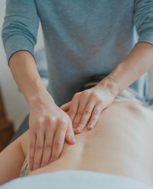 Womans hands massaging back.