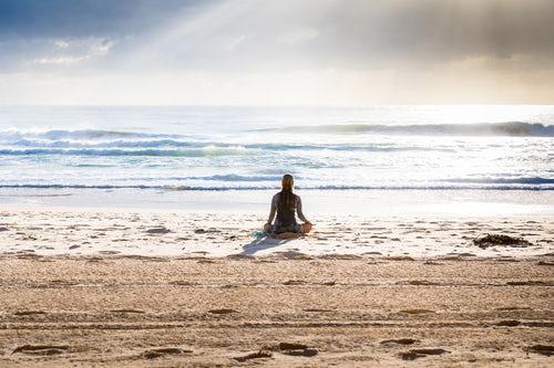 SITTING ON BEACH IN MEDITATION